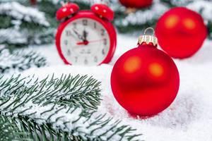Rote Weihnachtsbaumkugel im Schnee mit Tannenzweigen und rotem Wecker