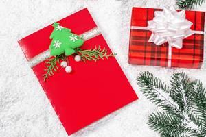 Rote Weihnachtsgrußkarte mit Geschenk und Tannenzweigen im Schnee