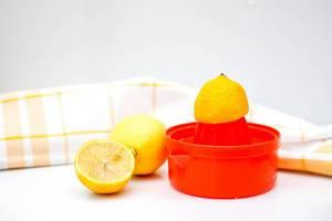 Rote Zitronenpresse und Zitronen