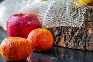 Roter Apfel und Mandarinen mit Wassertropfen im rustikalen Setting auf schwarzem Tisch