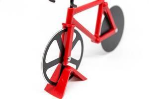 Roter Fahrrad-Pizzaschneider vor weißem Hintergrund