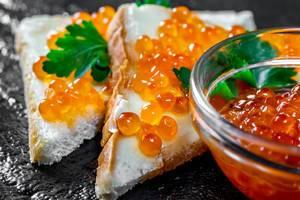 Roter Lachskaviar auf Weißbrot mit Petersilienblättern