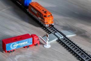 Roter Lastwagen wartet an der Schranke vor einem Bahnübergang, während ein Spielzeug-Zug vorbeifährt