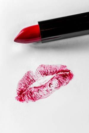 Roter Lippenstift neben rotem Lippenabdruck einer Frau auf weißem Papier