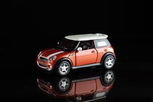 Roter Mini Cooper S mit weißem Dach und Streifen als Spielzeugauto vor schwarzem Hintergrund