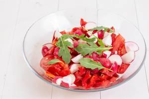 Roter Salat mit Tomate und Radieschen verfeinert mit Käse und Rucola in Schale