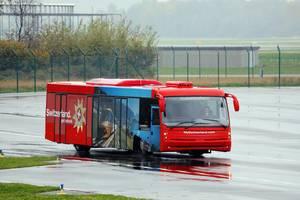 Roter Vorfeldbus vom Flughafen Zürich mit Werbung für Urlaub in der Schweiz