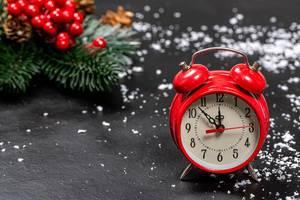 Roter Wecker mit einer Weihnachtsdekoration und Schneeflocken im Hintergrund