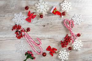 Roter Weihnachts Dekor und weisse Schneeflocken auf Holz Hintergrund mit Freiraum
