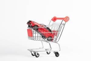 Rotes Auto in Einkaufswagen symbolisiert Anschaffung eines Fahrzeugs