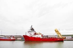 Rotes Frachtschiff in dänischen Ufern mit einem kleineren rotes Schiff nebenan