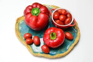 Rotes Gemüse - Rote Paprika mit Kirschtomaten auf blauem Tonteller