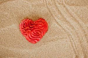 Rotes Herz auf dem Strandsand