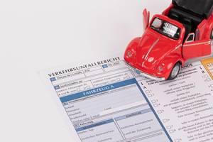 Rotes Oldtimer-Spielzeugauto auf einem Verkehrsunfallbericht