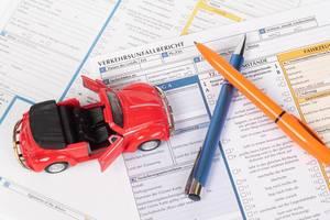Rotes Oldtimer-Spielzeugauto und zwei Kugelschreiber auf einem Autounfallbericht