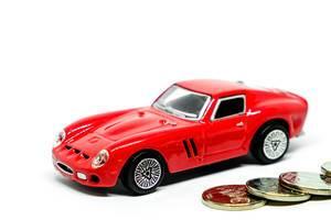 Rotes Spielzeugauto mit Münzen auf weißem Hintergrund