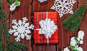 Rotes Weihnachtsgeschenk mit weißer Schleife umgeben vom Mistelzweigen und Schneeflocken