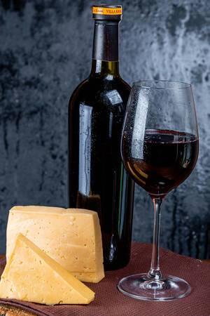 Rotwein in der Flasche und im Glas, neben gereiftem Käse, auf einem gedeckten Tisch vor schwarzem Hintergrund