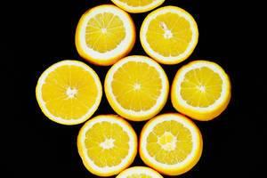 Round orange fruit slices on black background