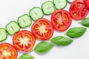Round pieces of cucumber, tomato and Basil leaves. Top view