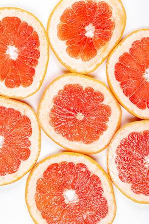 Round pieces of fresh grapefruit on a white background, top view