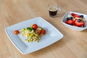 Rührei mit Tomaten, Obstsalat und Espresso