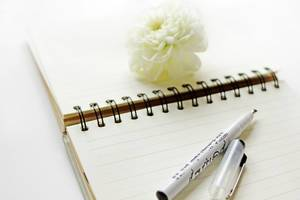 Ruled notebook with white flower and black marker on white background