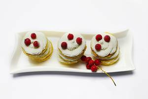 Runde gestapelte Kekse, gefüllt und dekoriert mit Schlagsahne und Johannisbeeren auf Teller