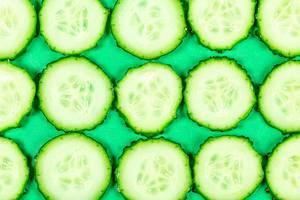 Runde Gurkenschneiden vor grünem Hintergrund, Aufnahme von oben
