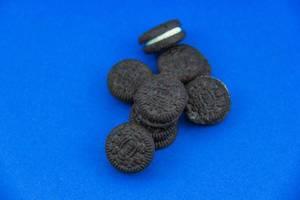 Runde Schokoladenkekse mit weißer Cremefüllung auf blauem Untergrund