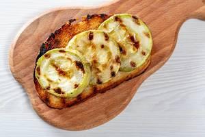 Runde Zucchinischeiben auf einer gegrillter Brotscheibe