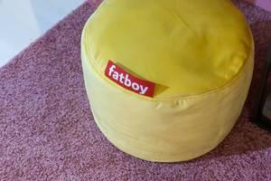 Runder Fatboy Sitzpuff aus gelbem Stoff auf flauschigem Teppich