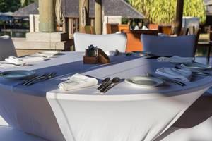Runder, gedeckter Tisch in weiß mit Stoffservietten auf der Restaurantterasse im Constance Ephelia Resort auf Mahé, Seychellen