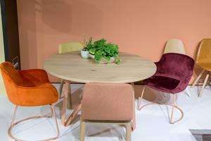 Runder Holztisch mit Blumendekoration umgeben von mit farbigem Stoff bezogenen Stühlen