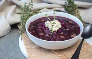Russische Borschtsch Suppe mit Rotkohl dekoriert mit Rosmarin in weißer Schüssel