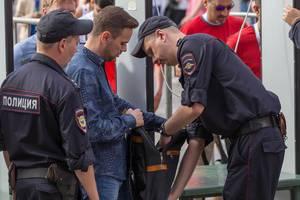 Russische Polizisten durchsuchen den Rucksack eines Mannes