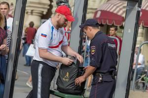 Russischer Polizist untersucht den Rucksack eines Fußballfans