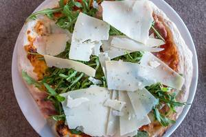 Rustic-style pizza with Parmesan, Rucola and Parma ham