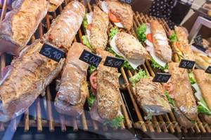 Rustikale Baguettes aus verschiedenen Brotsorten, belegt mit Salat, Wurst, Tomaten und Käse, in Barcelona (Spanien)