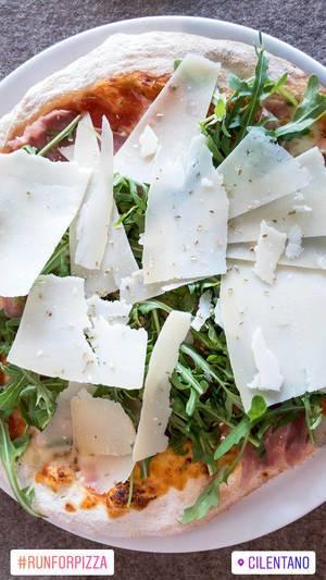 Rustikale Pizza mit Parmesan, Rucola und Parmaschinken