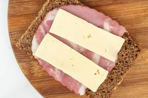 Rye Bread slice with Smoked Pork Neck on the wooden board and cheese