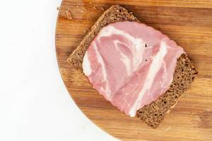 Rye Bread slice with Smoked Pork Neck on the wooden board