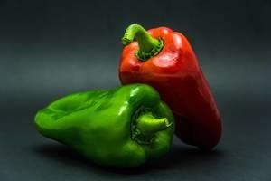 Saftige, rote und grüne ganze Paprika vor dunklem Hintergrund