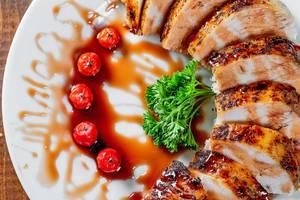 Saftige Scheiben gegrillte Hühnerbrust mit Soße, Tomaten und Petersilie auf einem Teller - Nahaufnahme
