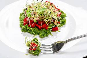 Salad layers with fresh vegetables and onion seed sprouts with fork on a white plate. Vegetarian and healthy food concept