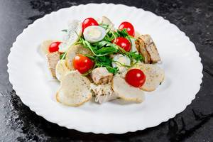 Salad with chicken fillet, vegetables, herbs, croutons and Parmesan