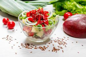Salad with fresh lettuce, pepper, tomatoes and mango with flax seeds and yogurt