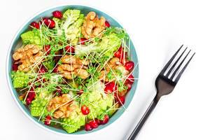 Salad with walnuts, pomegranate, watercress and vegetables on a white background, top view