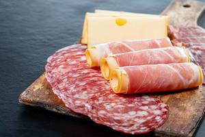 Salami, jamon, ham and cheese sliced on old kitchen wooden Board (Flip 2019)