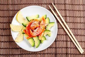 Salat mit Avocado-Scheiben, Räucherlachs, Sesamkernen und Zitronenscheiben auf einer Bambusmatte mit Essstäbchen Draufsicht